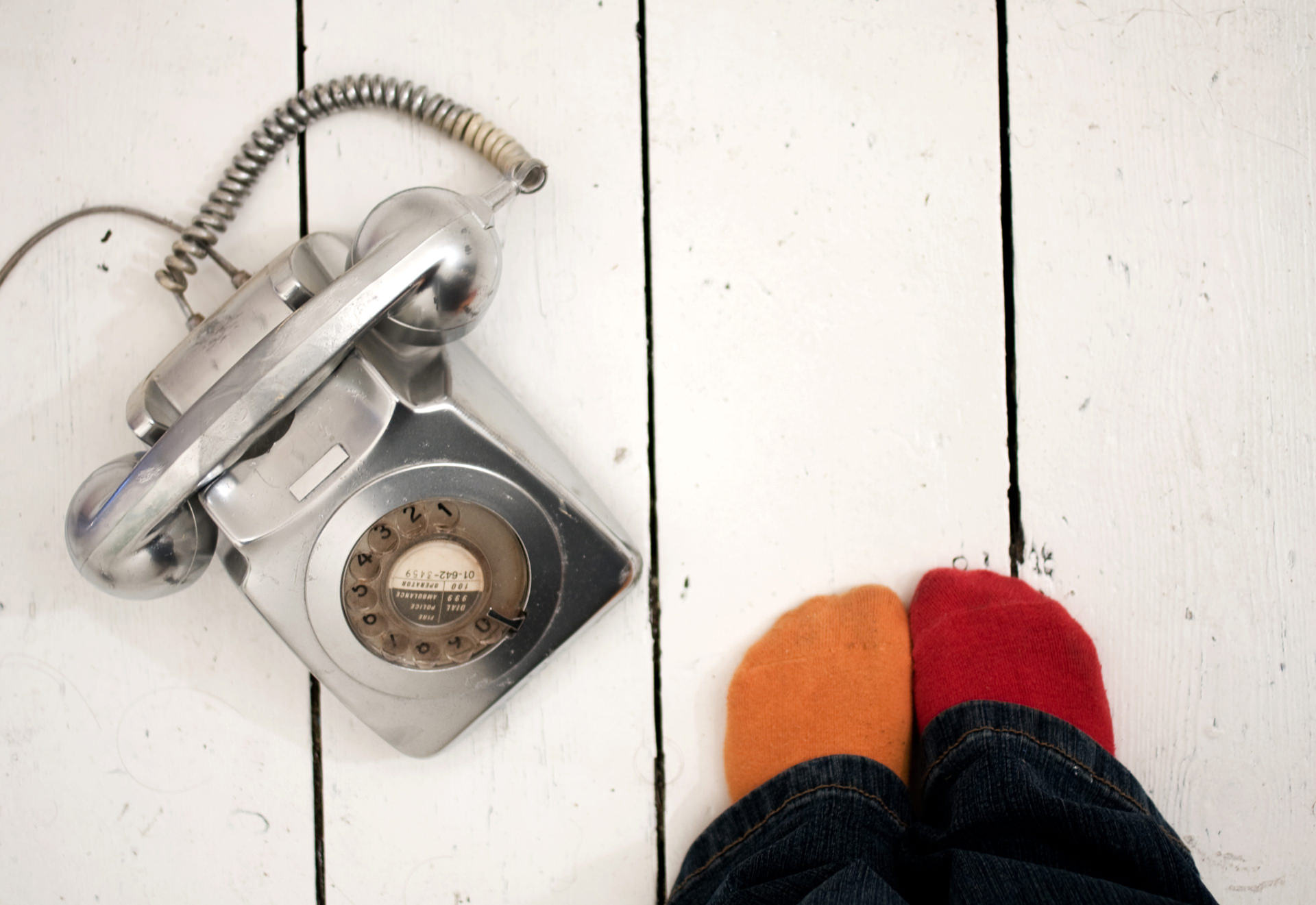 a silver phone next to orange and red socks - waiting a call picture by Laura Moreno