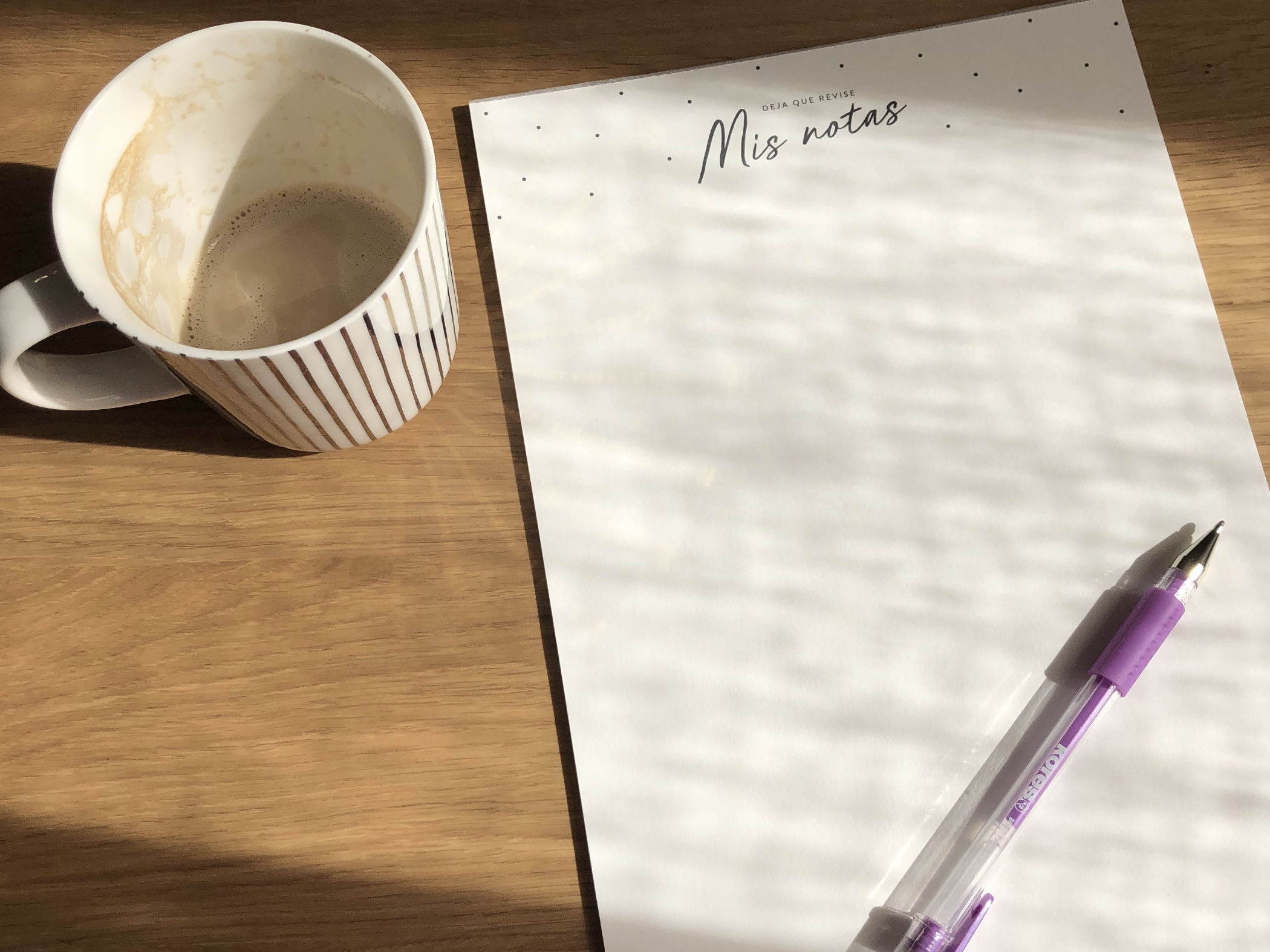 An almost empty cup of coffee next a Charuca notepack and purple pen